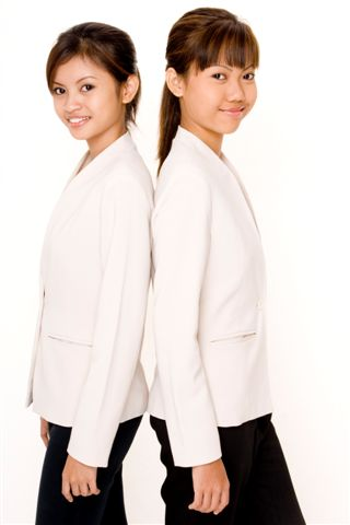 Two attractive young asian women in matching white jackets