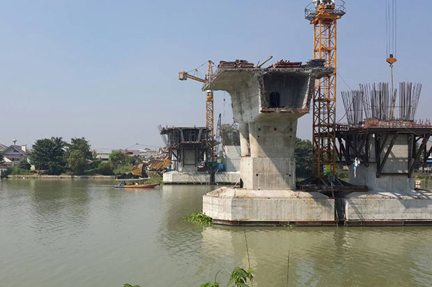 The toppled crane lies to the left of the far bridge pillar at the construction site on the Chao Phraya river bank between tambon Ko Rian and tambon Samphao Lom in Ayutthaya on Tuesday