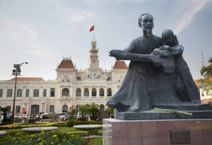 A statue of Ho Chi Minh stands in front of the City Hall building.