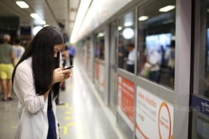A woman checks her mobile phone while waiting for the train arrival at an underground station in Bangkok.