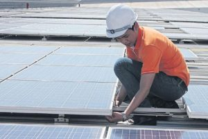 A worker installs solar panels in Samut Prakan province.