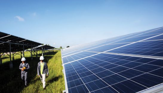 Workers walk past solar panels at the largest solar electricity plant in Thailand in 2014.